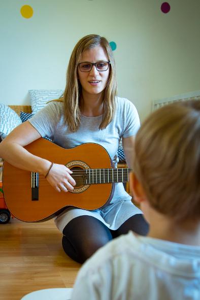Eli spielt auf Gitarre und singt im Musikkurs