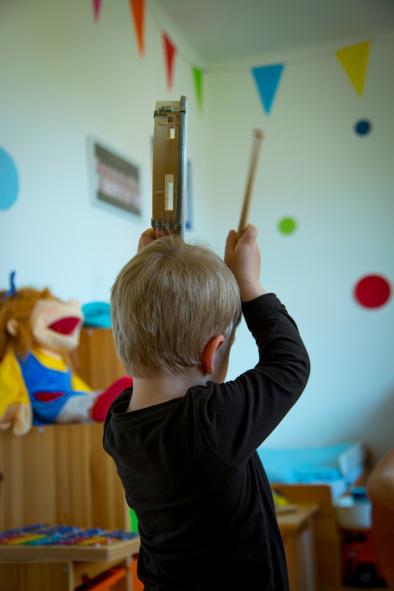 Kind trommelt im Musikkurs